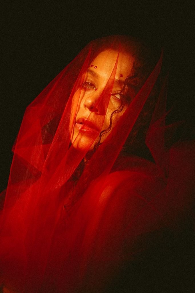 Dreamy girl wrapped in a red veil